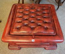 A Chesterfield Ox Blood Pouffe/Coffee Table, With a detachable top enclosing a glass surface, 33cm