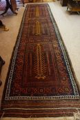 A Persian Bluch Rug, Hand Knotted, Decorated with allover geometric motifs on a red ground, 475cm