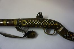 An Indian Flintlock Gun, circa early 19th century, Having a metal ramrod, The walnut stock and