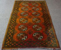 An Afghan Rug, Hand knotted, Decorated to the centre with six rows of two geometric medallions on an