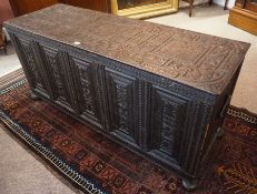 A Carved Oak Coffer, circa 18th century, Having a hinged top, Decorated with allover carved floral