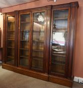A Victorian Gothic Style Oak Library Bookcase, Having four large glazed doors enclosing fifteen