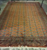 A Pakistani Bokhara Carpet, Decorated with multiple rows of geometric motifs on a red ground,