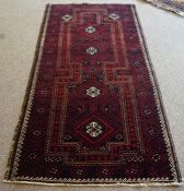 A Persian Bluch Rug, Hand knotted, Decorated with allover geometric motifs on a red and blue ground,