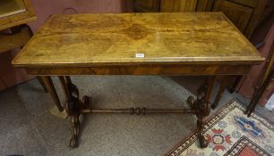 A Victorian Walnut Card Table, Having a fold over top, enclosing a green felt lined interior, raised