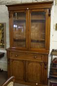 A Victorian Plum Pudding Mahogany Bookcase on Secretaire Base, Having two glazed doors, enclosing