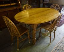 An Ercol Dining Table with Four Windsor Style Chairs, The D end table is raised on barley twist
