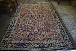 A Persian Carpet, Decorated with allover floral panels, on a pink ground, with a blue and cream