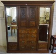 A Late Victorian Walnut Wardrobe, Having two cupboard doors above four drawers, flanked with a