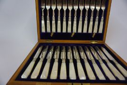 A Set of Twelve Silver Plated and Mother of Pearl Fruit Knives and Forks, In a fitted box