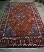 A Joshgan Carpet, Decorated with allover geometric motifs, on a red ground, 315cm x 205cm