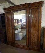 A Victorian Mahogany Breakfront Three Door Wardrobe, Having a moulded cornice above a mirrored door,