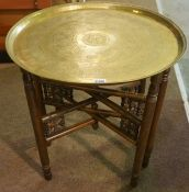 An Indian Style Brass Top Table, raised on folding supports, 58cm high, 53cm wide