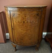 A Walnut Demi Lune Cupboard, Having a cupboard door enclosing two small drawers, raised on