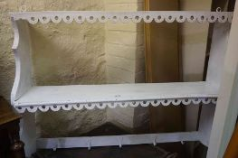 A Set of White Painted Hanging Wall Shelves, Having five pegs to the lower shelve for hat and coats,
