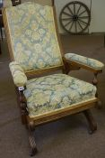 An Oak Framed Rocking Chair, Upholstered in later floral fabric, raised on castors, 99cm high