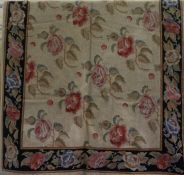 An Old English Style Needlepoint Rug, Decorated with allover floral panels, on a beige ground with