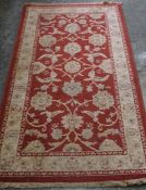 A Small Persian Style Rug, Decorated with floral swags on a red ground, with cream border, 161cm x