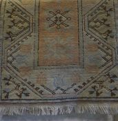 A Turkish Rug, Decorated with geometric and floral motifs, on a cream and pink ground, 150cm x 80cm