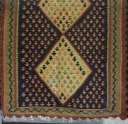 A Kilim Rug, Decorated with three large beige diamond medallions to the centre, on a red and blue