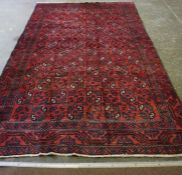 A Turkoman Rug, Decorated with allover geometric motifs, on a red ground, 280cm x 180cm