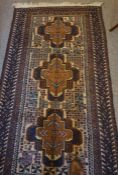 An Afghan Bluch Rug, Having three large geometric medallions to the centre, on a brown ground, 200cm