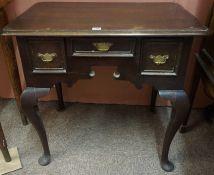 A Georgian Oak Lowboy, Having a single drawer, flanked with a deeper drawer, raised on cabriole legs