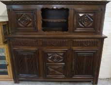 An Oak Press / Cupboard, 20th century, Having an open recess, flanked with a carved door, above