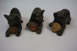 Three Similar Bretby Terracotta Cat figures, each figure having glass eyes and holding a ball,