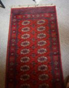A Wilton Persian Style Rug, Decorated with nine rows of two geometric medallions, on a red ground,
