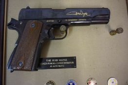 The John Wayne Armed Forces Commoemorative Replica 45 Automatic Pistol, by Franklin Mint, in a frame