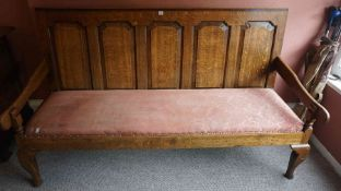 An Oak Hall Bench, in the 18th century style, Having a panelled back rest, above a later upholstered