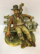 A Capo Di Monte Figure, Modelled as a drunk sitting on a garden bench, having gilded decoration