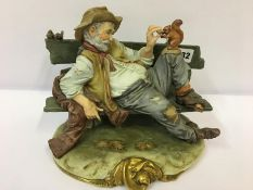 A Capo Di Monte Style Figure Group, Modelled as a drunk laying on a garden bench feeding a squirrel,