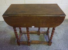 A Vintage Oak Drop Leaf Table, Raised on barley column legs, 68cm high, 77cm wide and long