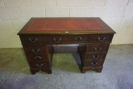 Reproduction Kneehole Desk, Having a tooled red leather skiver above three assorted drawers,