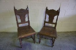 A Pair of Carved Oak Hall Chairs, Carved with panels of scrolls and acanthus leaves, raised on