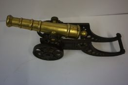 Antique Brass Model of a Cannon, Raised on a tilting iron cart wheel, 18cm high, 47cm long, also