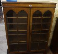 Walnut Bookcase, Having two glazed doors enclosing a shelved interior,