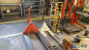 Lot of two assorted hydraulic pallet jacks and three assorted hand trucks. Both pallet jacks work