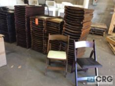 Lot of (85) assorted brown wood folding chairs, (60) with tan pads, and (25) with black pads.