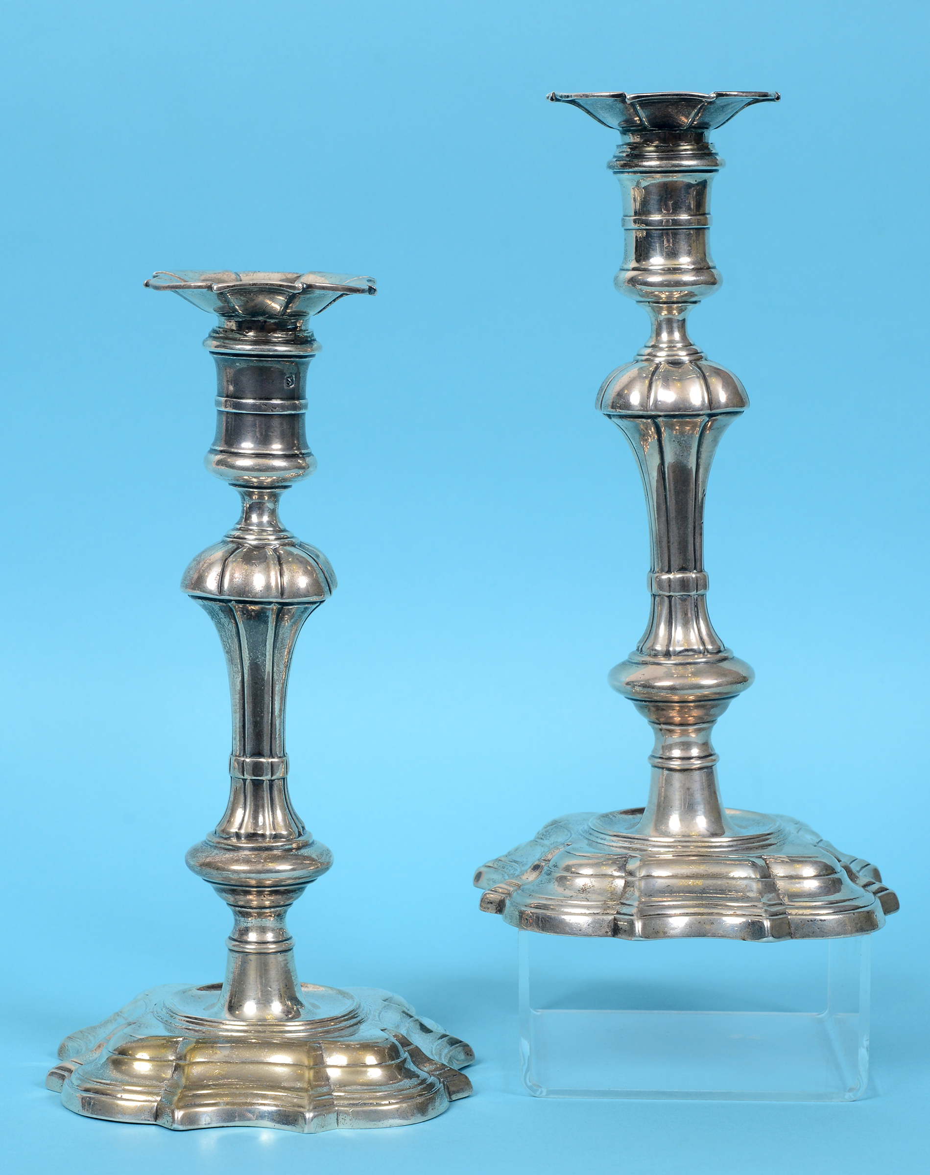 Lot 174 - A pair of George II cast silver candlesticks, with detachable sconces, on spreading shaped square
