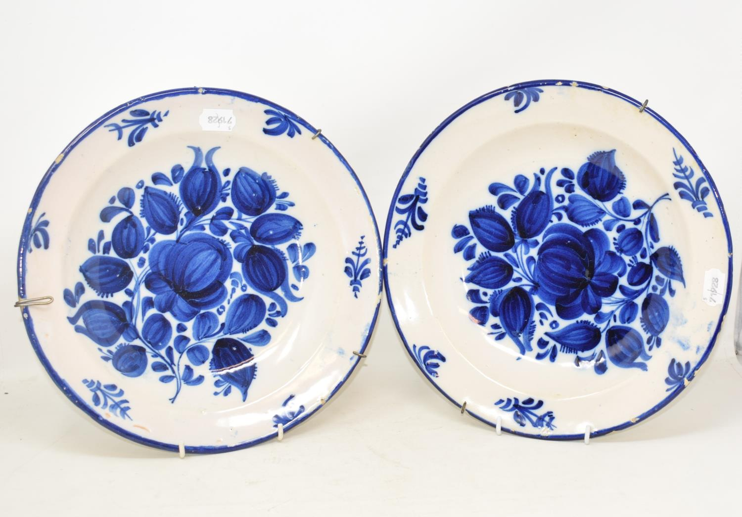 Lot 5 - A pair of tin glazed blue and white bowls, decorated flowers, 31.5 cm diameter, two pottery meat