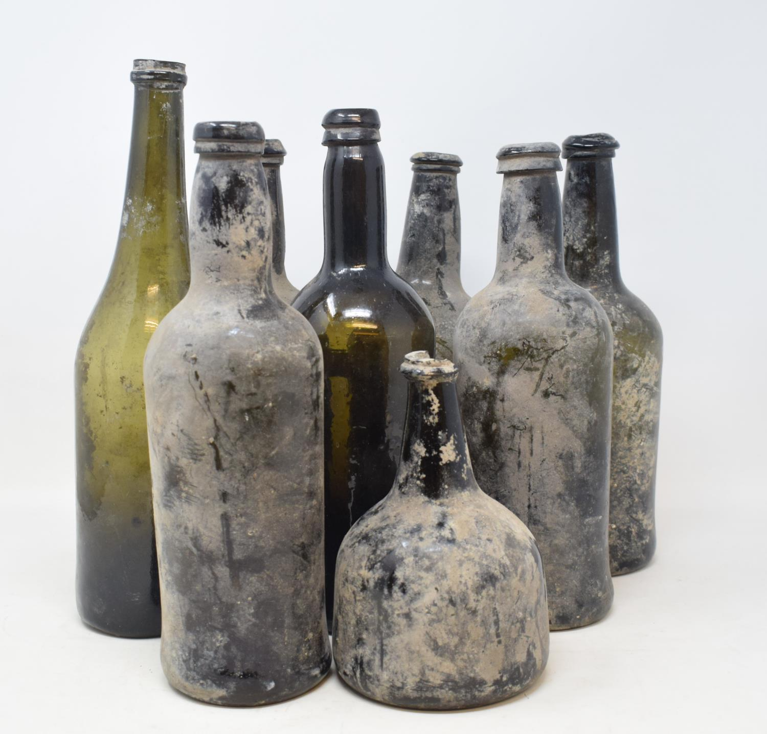 Lot 17 - An 18th century glass wine bottle, of mallet form, rim chipped, 17 cm high, and seven 19th century