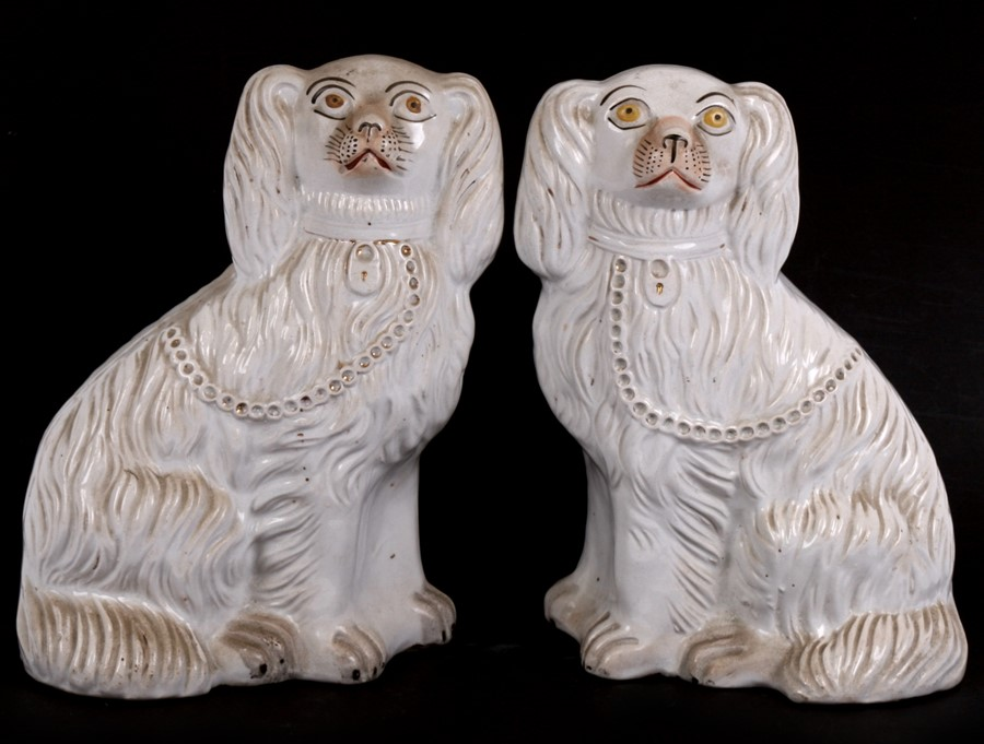 Lot 51 - A pair of Victorian Staffordshire spaniels, 28cms (11ins) high.