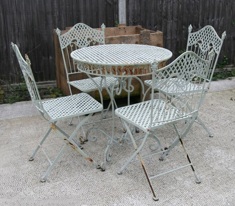 Lot 2 - A green painted metal garden table and four matching chairs, the table 75cms (29.5ins) diameter.