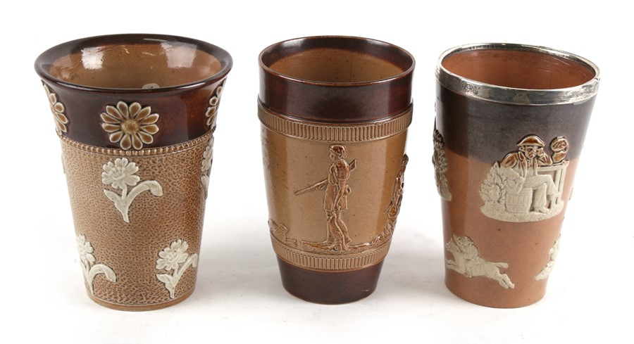 Lot 22 - A Royal Doulton Stoneware silver mounted beaker; together with two other similar beakers, 12cms (4.
