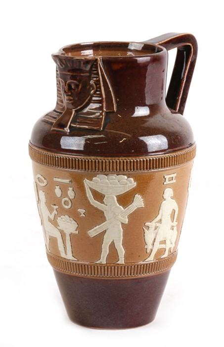 Lot 25 - A stoneware jug decorated with Egyptian figures, 17cms 96.5ins) high.