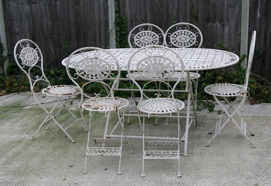 Lot 1 - A white painted metal garden table and six matching chairs, the table 160cms (63ins) wide.