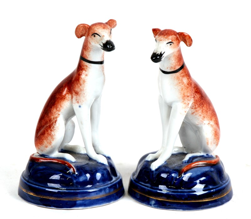 Lot 101 - A pair of seated porcelain dogs with gold anchor mark to underside, 10cms (4ins) high.